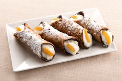 Four cannoli Sicilia with creamy ricotta filling. Four deep fried cannoli Sicilia pastries with creamy ricotta filling garnished with orange rind and served on a royalty free stock image