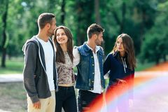 Four carefree young people walking in park on sunny day Royalty Free Stock Photo