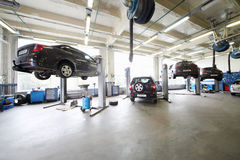 Four cars on lifts and on floor in small service station. Stock Images