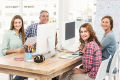 Four casual colleagues using computer Royalty Free Stock Photos