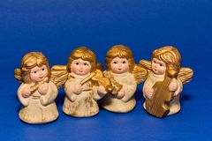 Four of ceramic small angels with music instruments Royalty Free Stock Photography