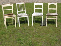 Four chairs. Four restoration-needy chairs that are offered by an antique dealer for sale stock photos
