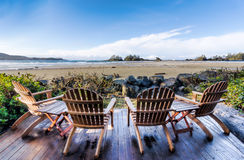 Four Chairs on Deck Overlooking Beach Royalty Free Stock Photos