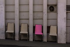 Four chairs and one is special. Pink unique chair stock image