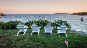 Four chairs overlook the bay at sunset. Four chairs overlook Linekin Bay at sunset in Boothbay Harbor, Maine Royalty Free Stock Photo
