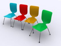 Four Chairs in a Row. Four colorful chairs in red, yellow, blue and green aligned in a row Royalty Free Stock Images