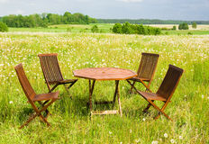 Four chairs and table. In the grassland Royalty Free Stock Photos