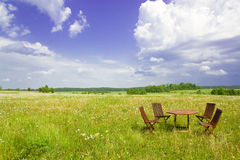 Four chairs and table. In the grassland Stock Photography