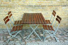 Four chairs and table in beer garden on brick wall, top view Stock Images