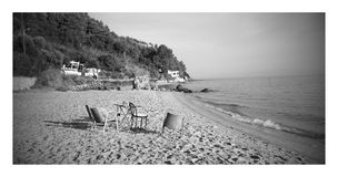 Four chairs and a table lying on the sand. Black & white Stock Photography