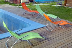 Four chaise-longues stand at the empty pool on a cloudy day. Four chaise-longues stand at the empty pool on cloudy day stock photos
