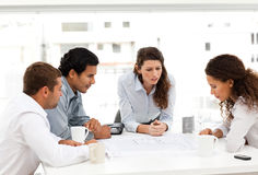 Four charismatic architects looking at plans. Together around a table Stock Photography