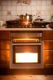 Four chaud et casserole bouillant sur le fourneau à la cuisine Images libres de droits