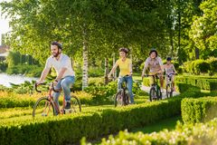 Four cheerful friends cycling outside. Group of young happy persons riding bicycles outdoors. Summer leisure with bicycles royalty free stock photo