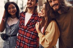 Four cheerful friends hugging and looking happy together royalty free stock photography