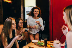 Four cheerful girlfriends having fun chatting and laughing eating and drinking in fast food restaurant.  stock images