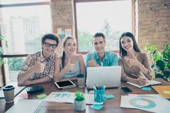 Four cheerful glad satisfied people, guys and girls, friends sit royalty free stock image