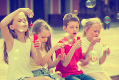 Four cheerful kids blowing soap bubbles Royalty Free Stock Photo