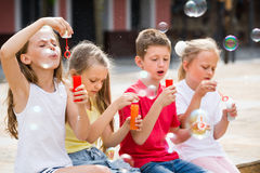 Four cheerful kids blowing soap bubbles Stock Image
