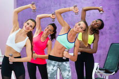 Four cheerful women holding dumbbells while doing exercises duri. Four cheerful women holding dumbbells while doing exercises for arms and lateral abdominal Stock Image