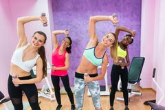 Four cheerful women holding dumbbells while doing exercises duri. Four cheerful women holding dumbbells while doing exercises for arms and lateral abdominal Stock Photography
