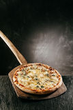 Four Cheese Italian Pizza on a restaurant menu. With a flame grilled steaming hot pizza served on a wooden board in front of a blank chalkboard with copyspace Royalty Free Stock Photos