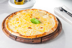 Four cheese pizza quattro fromaggi with basil leaf on a rustic wooden board Stock Photos