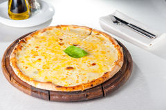 Four cheese pizza quattro fromaggi with basil leaf on a rustic wooden board Stock Photo