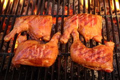 Four Chicken Leg Quarter Roasted On Hot BBQ Flaming Grill Royalty Free Stock Image