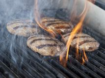 Four Chicken meat burger steaks on the grill with flames. cookin. G chicken grilling or bbq or barbecue on charcoals. Close up Royalty Free Stock Images