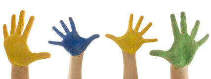 Four child hands painted. In blue, yellow and green stock images