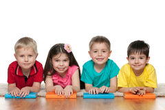 Four children with books. Are lying on the floor Royalty Free Stock Photo