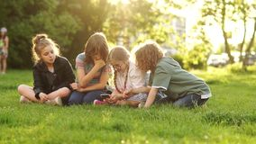 Four children, boys and girls watch and discuss the smartphone in the hands of one of them. Kids and Gadgets Back to