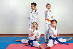 Four children demonstrate martial arts working together. Fighting position, active lifestyle, expressing emotions royalty free stock photos
