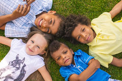 Four children are laying on the glade. Royalty Free Stock Photo