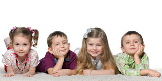 Four children lying on the carpet Stock Photo