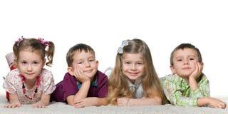 Four children lying on the carpet Stock Photo