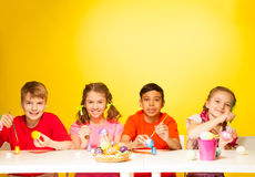 Four children paint Easter eggs at the table Royalty Free Stock Photos