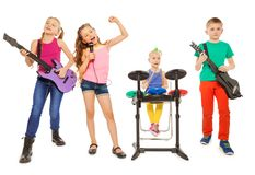 Four children perform together as rock group. And girl singing as vocalist in front on white background Royalty Free Stock Photography