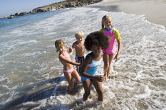 Four children (6-10) playing in Atlantic surf at beach, side view, smiling (wide angle, tilt) Stock Photography