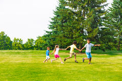 Four children are playing on the glade. Royalty Free Stock Photo
