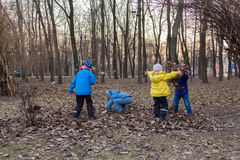 Four children playing with last year foliage in park Stock Photos