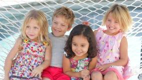 Four Children Relaxing In Garden Hammock Together stock video footage
