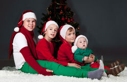 Four children sitting around Christmas tree. Royalty Free Stock Images