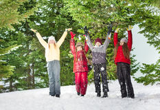 Four children standing in row at the winter forest Royalty Free Stock Image