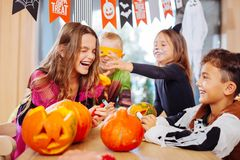 Four children wearing Halloween costumes laughing out loud during the party royalty free stock photos