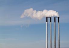 Four chimneys on a blue sky. Four chimneys and smoke on a blue sky Stock Photos