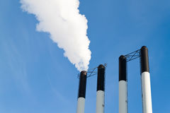 Four chimneys on a blue sky. Four chimneys and smoke on a blue sky Royalty Free Stock Photos