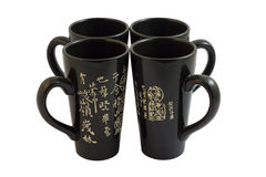 Four chinese cups. Four black chinese cups isolated on white Royalty Free Stock Photography