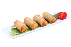 Four Chinese spring rolls on a white long, narrow plate. Royalty Free Stock Image